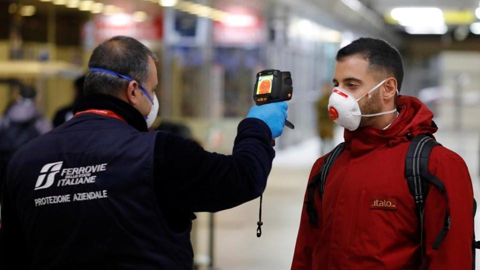 A train security staff member checks the temperature of a passenger arriving from Turin and Milan by train at Naples Central station as Italy ramps up measures to slow the spread of coronavirus in Naples, Italy on  March 22, 2020.