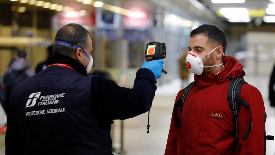 A security staff member checks the temperature of a passenger arriving from Turin and Milan by train, at Naples Central station in Italy on March 22.