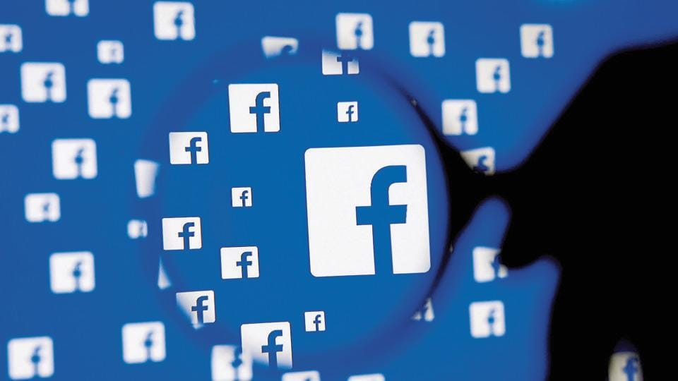 A man poses with a magnifier in front of a Facebook logo on display in this illustration taken in Sarajevo, Bosnia and Herzegovina, December 16, 2015. REUTERS/Dado Ruvic/Illustration/File Photo GLOBAL BUSINESS WEEK AHEAD PACKAGE - SEARCH