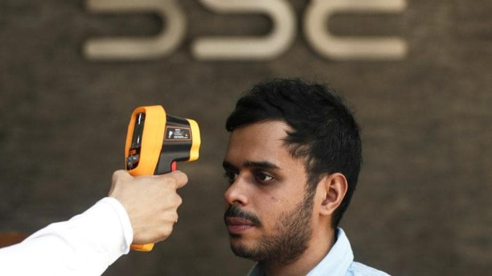 A security official scans a visitor with an infrared thermometer to check his temperature as a precautionary measure against coronavirus outside the Bombay Stock Exchange (BSE), Mumbai, March 16, 2020