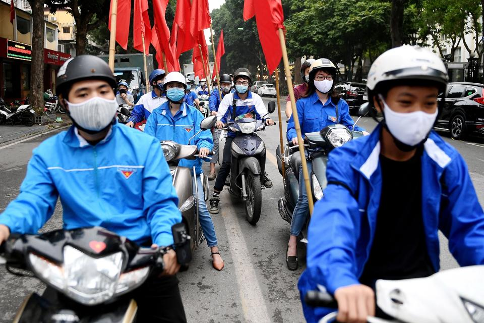 People wearing face masks take part in a motorcade as a public awareness campaign for the prevention of the spread of COVID-19 novel coronavirus in Hanoi on March 23, 2020.
