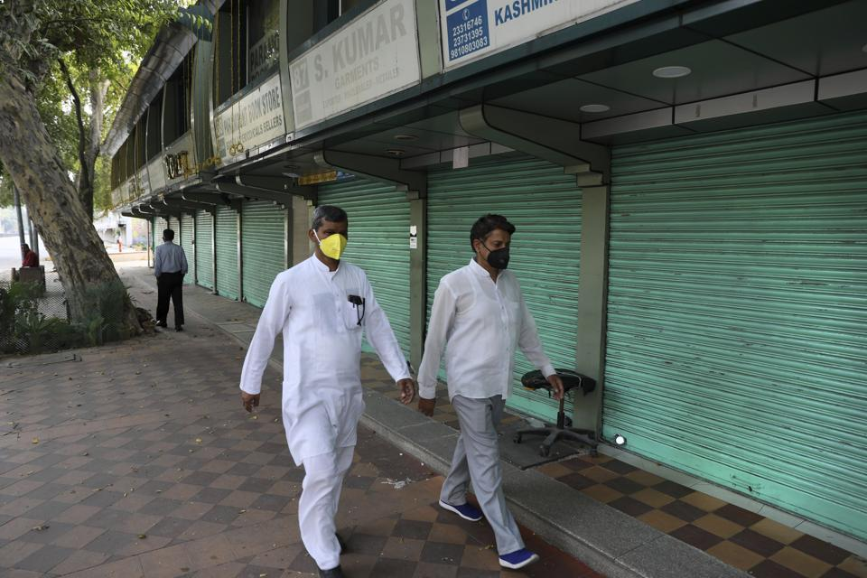 Indians wearing face masks as a precaution against coronavirus walk past closed shops on the first day of a lockdown amid concerns over the spread of Coronavirus, in New Delhi, India, Monday, March 23, 2020. Authorities have gradually started to shutdown much of the country of 1.3 billion people to contain the outbreak. For most people, the new coronavirus causes only mild or moderate symptoms. For some it can cause more severe illness. (AP Photo/Manish Swarup)