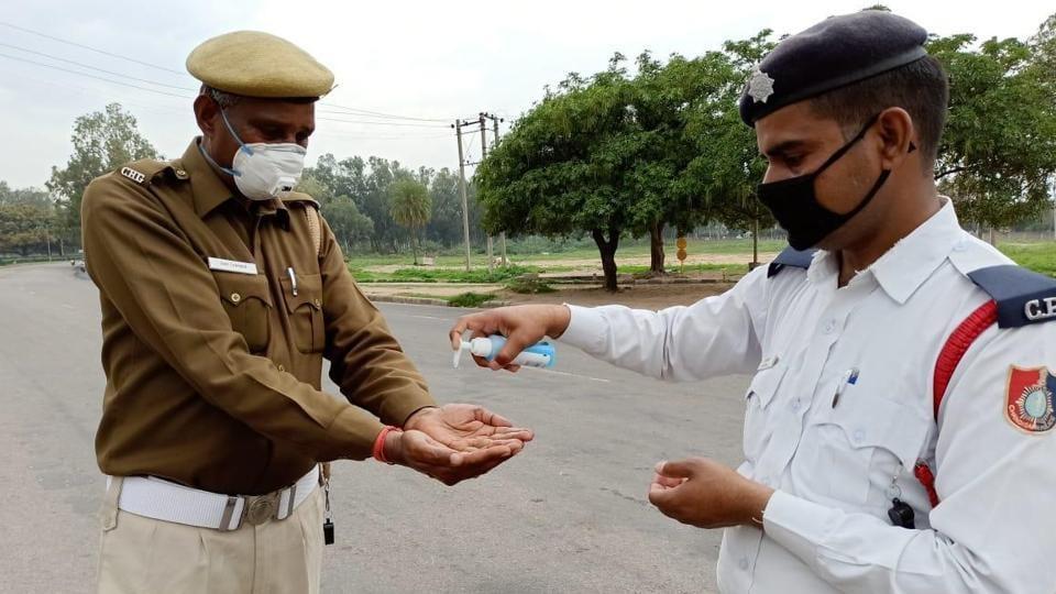 CoronavbiruPolice officials sanitize their hands at housing board light point in Chandigarh.