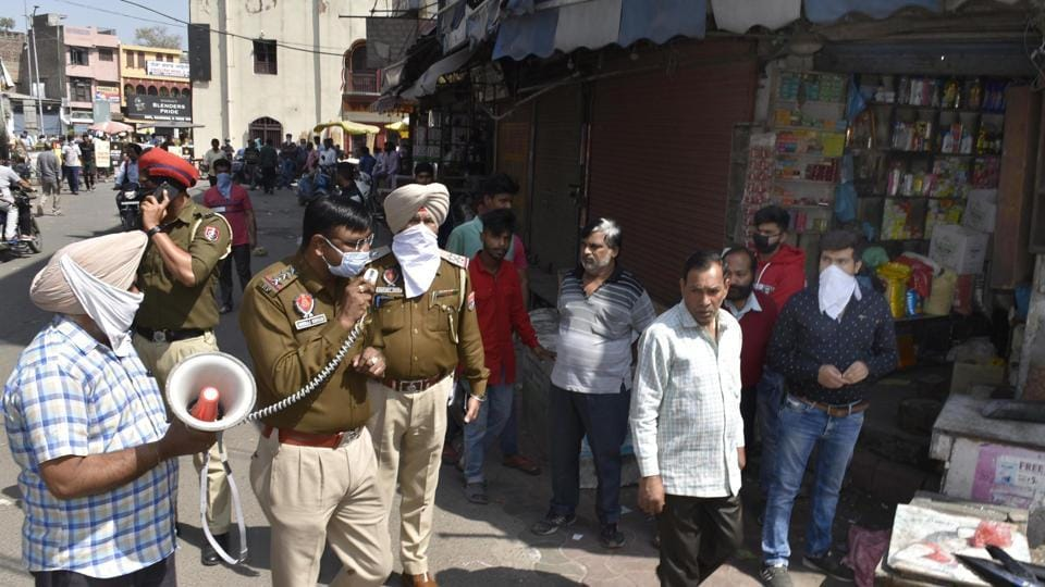 Punjab Police personnel make announcement on a loudspeaker informing the crowd on the state lockdown to control the spread of coronavirus, at Crystak Chowk in Amritsar on Monday.