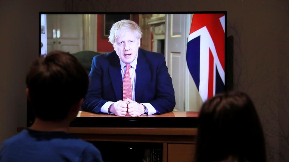 Two children watch British Prime Minister Boris Johnson's press conference on Monday as the spread of coronavirus disease Covid-19 continues in Hertford.