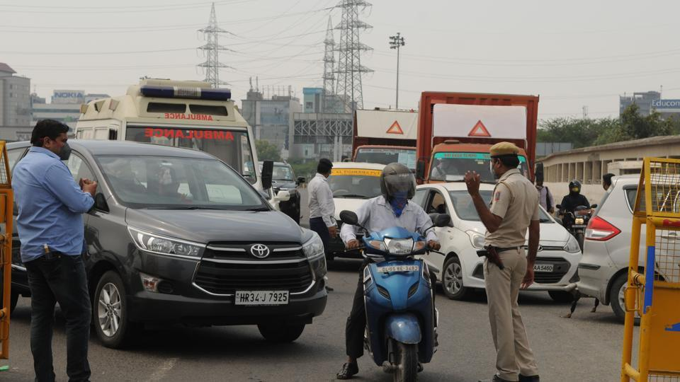 Police personnel direct commuters at Delhi-Gurugram border after it was sealed during the second day of lockdown imposed by the state government to curb the spread of coronavirus, on Tuesday.