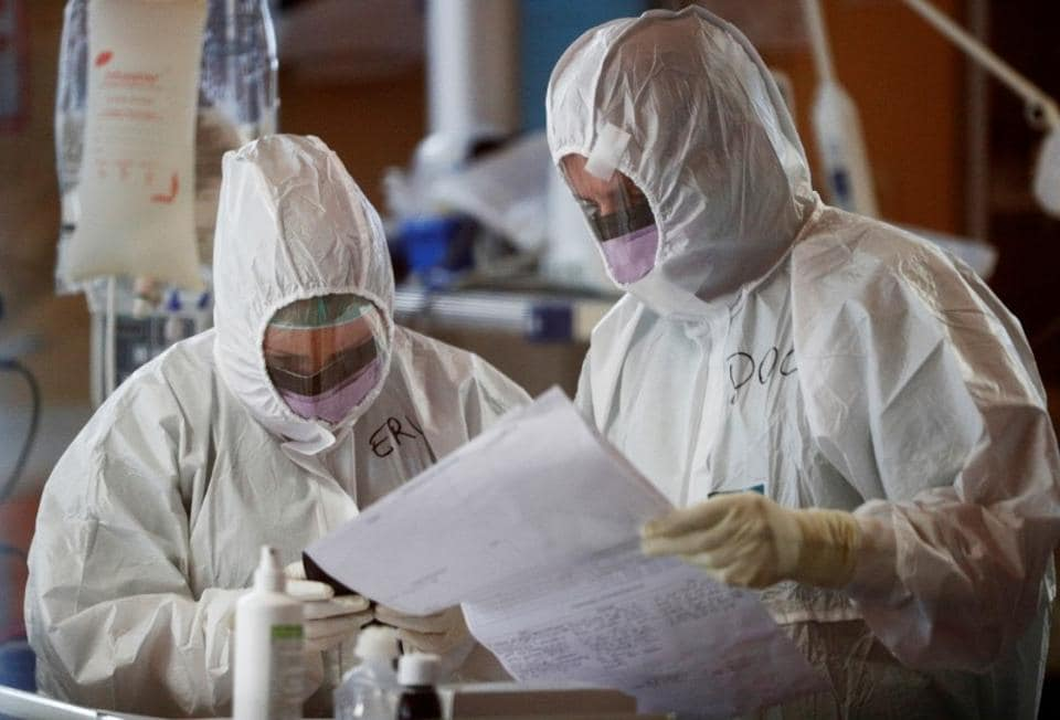 Medical workers in protective suits check a document as they treat patients suffering with coronavirus disease (COVID-19) in an intensive care unit at the Casalpalocco hospital, a hospital in Rome that has been dedicated to treating cases of the disease, Italy, March 24, 2020.