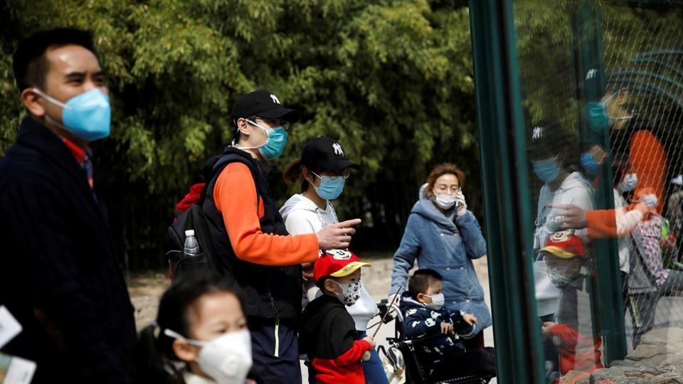 People wearing face masks visit Beijing Zoo, which has partially reopened after closing in late January due to the coronavirus disease (COVID-19) outbreak, in China, March 24, 2020.