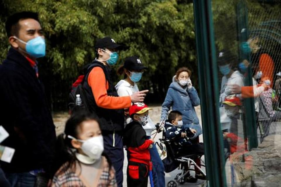 People wearing face masks visit Beijing Zoo, which has partially reopened after closing in late January due to the coronavirus disease (COVID-19) outbreak, in China on March 24, 2020.