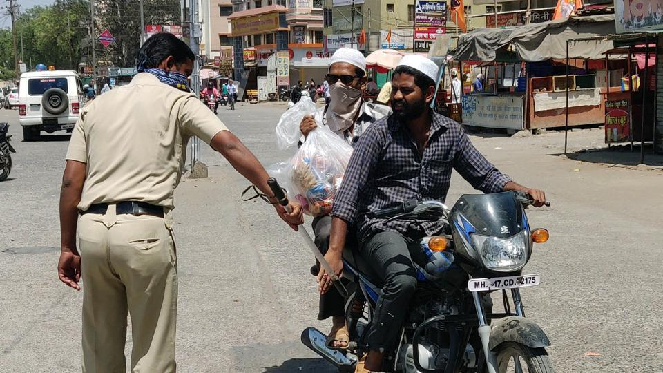 Police personnel taking action against people riding bikes on the road during the lockdown, in Maharashtra' Kopergaon on Monday.