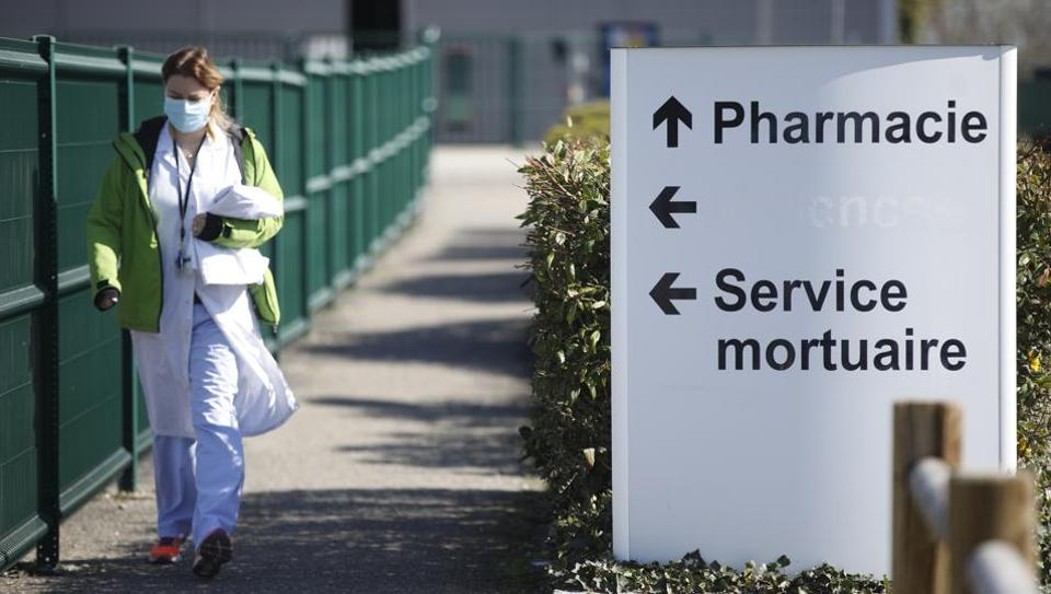 A medical staff walks by the civil hospital in Mulhouse, eastern France, Tuesday, March 24, 2020. The Grand Est region is now the epicenter of the outbreak in France, which has buried the third most virus victims in Europe, after Italy and Spain. For most people, the new coronavirus causes only mild or moderate symptoms. For some it can cause more severe illness.