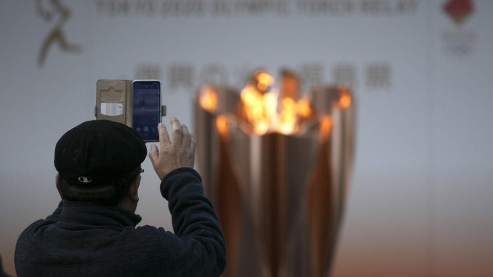 A man takes pictures of the Olympic Flame during a ceremony in Fukushima City, Japan, Tuesday, March 24, 2020