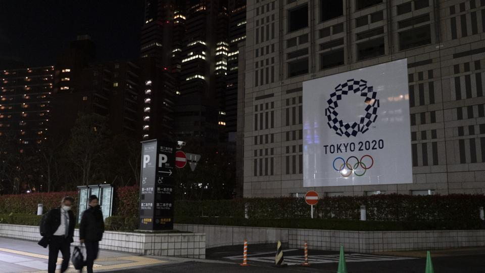 Two men walk past a large banner promoting the Tokyo 2020 Olympics in Tokyo.