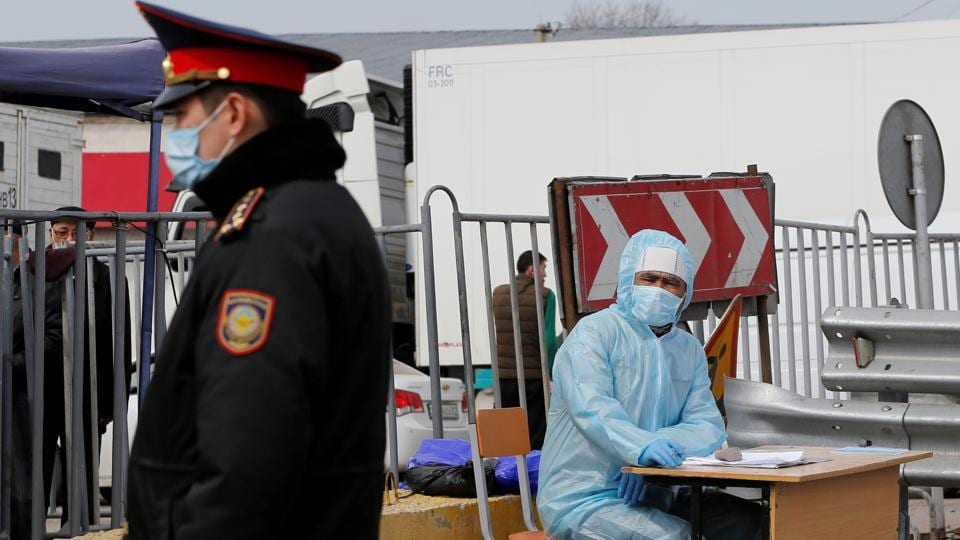 An official wearing protective gear works at a checkpoint set up to lock down the city to prevent the spread of coronavirus disease (COVID-19), on the outskirts of Almaty, Kazakhstan.