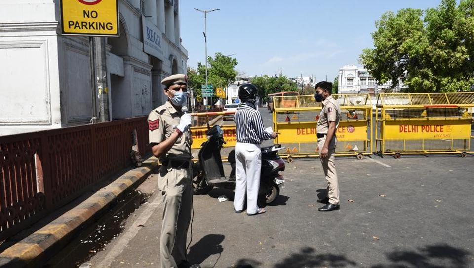 A Delhi Police personnel directs people on a loud speaker to stay indoors during a national lockdown to curb the spread of coronavirus, outside Regal theater, at Connaught Place, in New Delhi.