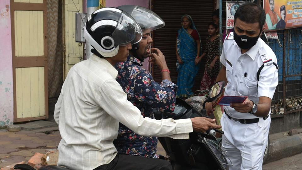 A  policeman  check the identity of people out during lockdown due to coronavirus outbreak, in Kolkata, West Bengal, on Tuesday, March 24, 2020.