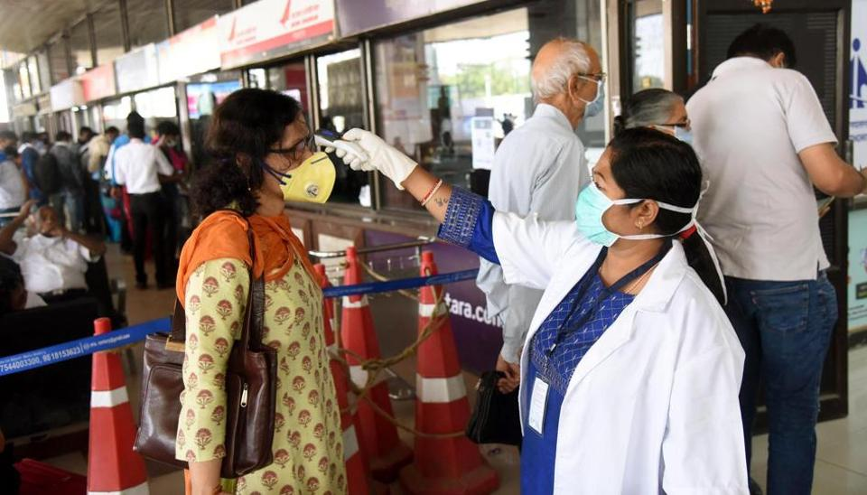 A passenger undergoes thermal screening at the departure corridor of Patna Airport during the second day of lockdown imposed by the state government to curb the spread of coronavirus, in Bihar, India, on Tuesday, March 24, 2020.