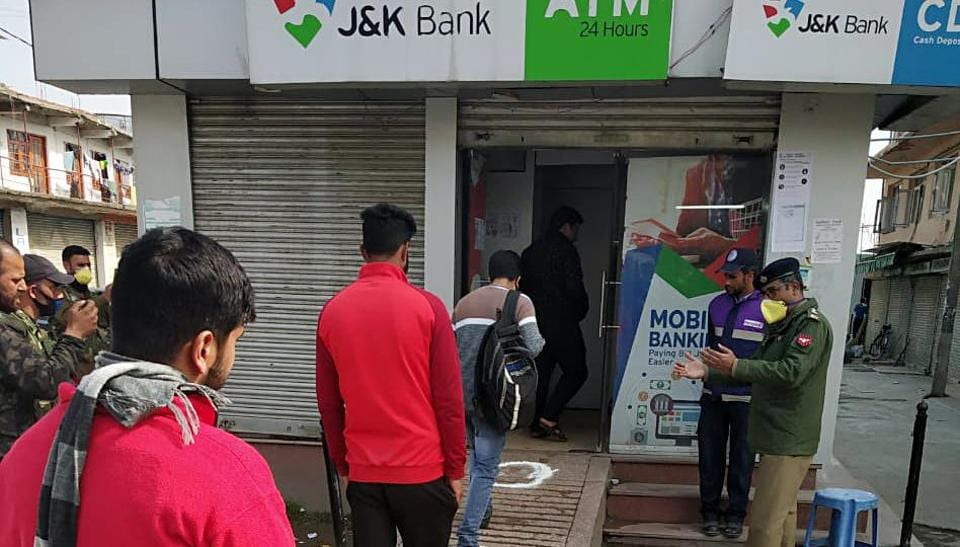 People standing at one meter distance que up to withdraw money from the ATM as a precautionary measure due to increasing cases of coronavirus, in Srinagar.