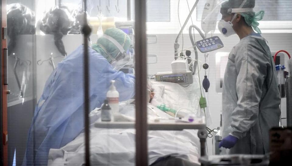 In this Thursday, March 19, 2020, file photo, medical personnel work in the intensive care unit of a hospital in Brescia, Italy.