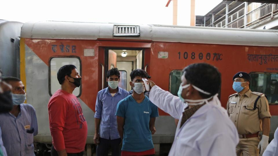 A railways official checks temperature of a railway worker in Prayagraj, India, Tuesday, March 24, 2020. Indian Prime Minister Narendra Modi Tuesday announced a total lockdown of the country of 1.3 billion people to contain the new coronavirus outbreak. For most people, the new coronavirus causes only mild or moderate symptoms. For some it can cause more severe illness.
