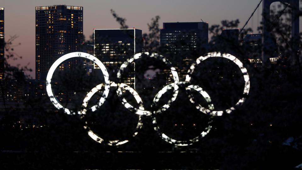 The giant Olympic rings are seen in the dusk through a tree at the waterfront area at Odaiba Marine Park.