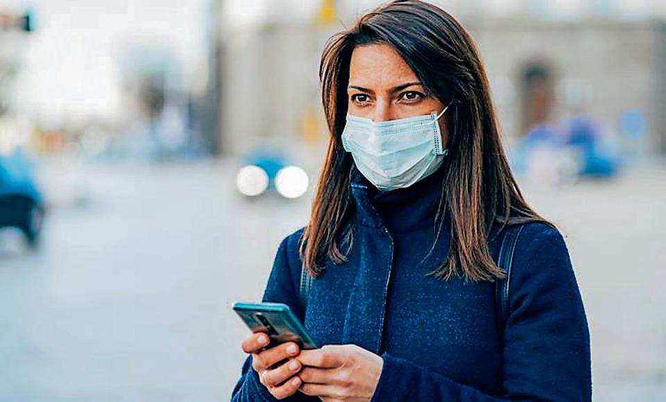 Portrait of young woman on the street wearing face protective mask to prevent Coronavirus and anti-smog and using smartphone