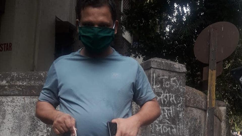 A volunteer from Project Mumbai carries grocery bags with the tagline - Mumbai ke liye kuch bhi karega