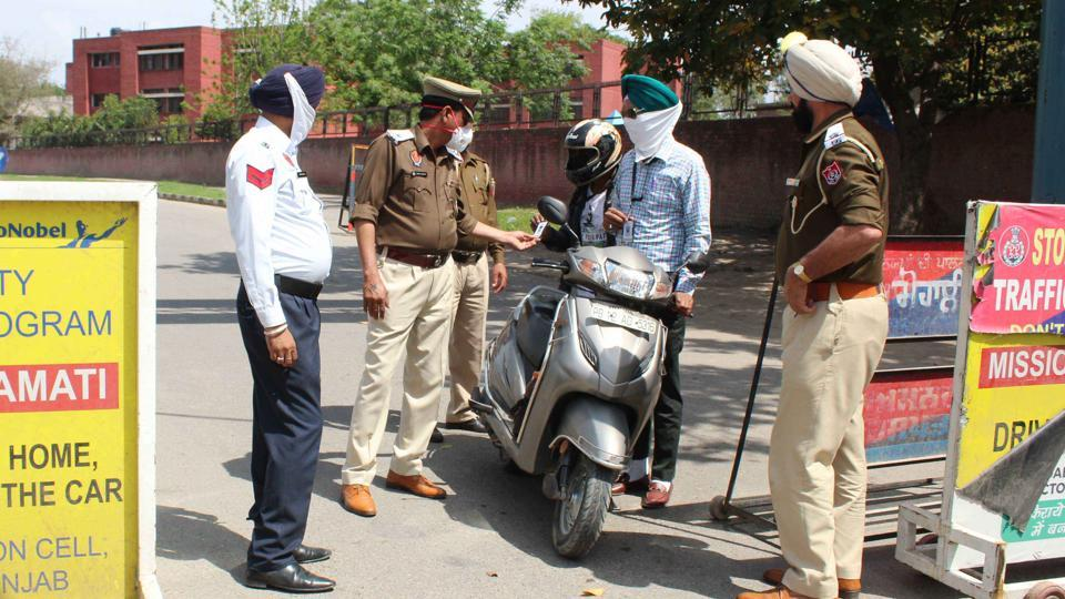 Policemen checking residents who stepped out of their houses at the Phase 3A barrier in Mohali amid the curfew in Punjab on Wednesday.