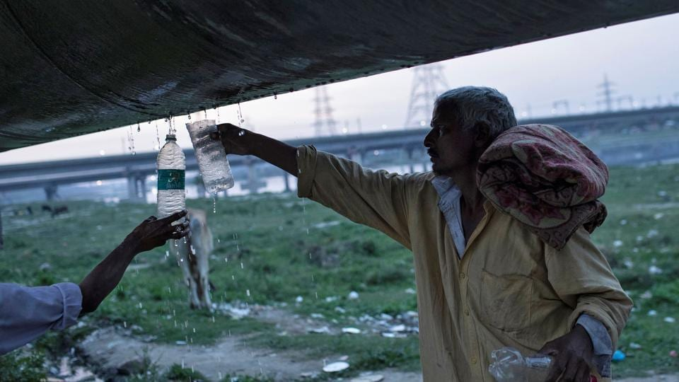 A homeless man fills water from a broken water pipeline as he waits for food outside a government-run night shelter during a 21-day nationwide lockdown to limit the spreading of coronavirus disease (COVID-19) in New Delhi.