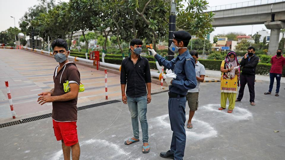 A security guard uses an infrared thermometre to measure the temperature of people standing in circles drawn with chalk to maintain safe distance as they wait to enter a supermarket during the coronavirus disease Covid-19 outbreak in New Delhi, on March 25.
