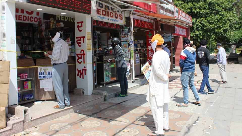 Residents maintaining appropriate distance while buying medicines at cordoned off pharmacies in Phase 3B2, Mohali.