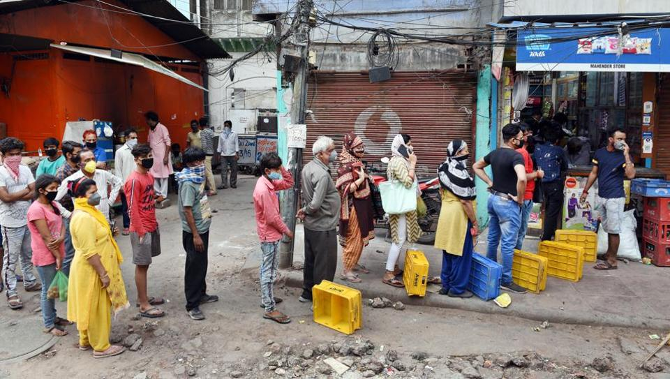 People queue to buy groceries and vegetables outside a store at Delhi's Sitaram Bazaar on day 2 of the three week nationwide lockdown to check the spread of coronavirus.
