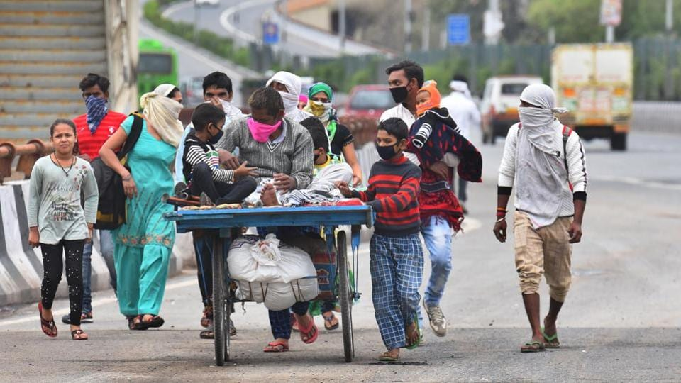 Ram Avatar, a migrant worker is seen on a hand push cart with his family as they make their way home to Sambhal district in Uttar Pradesh during the 21-day national lockdown at NH24, in New Delhi. (Raj K Raj / HT Photo)
