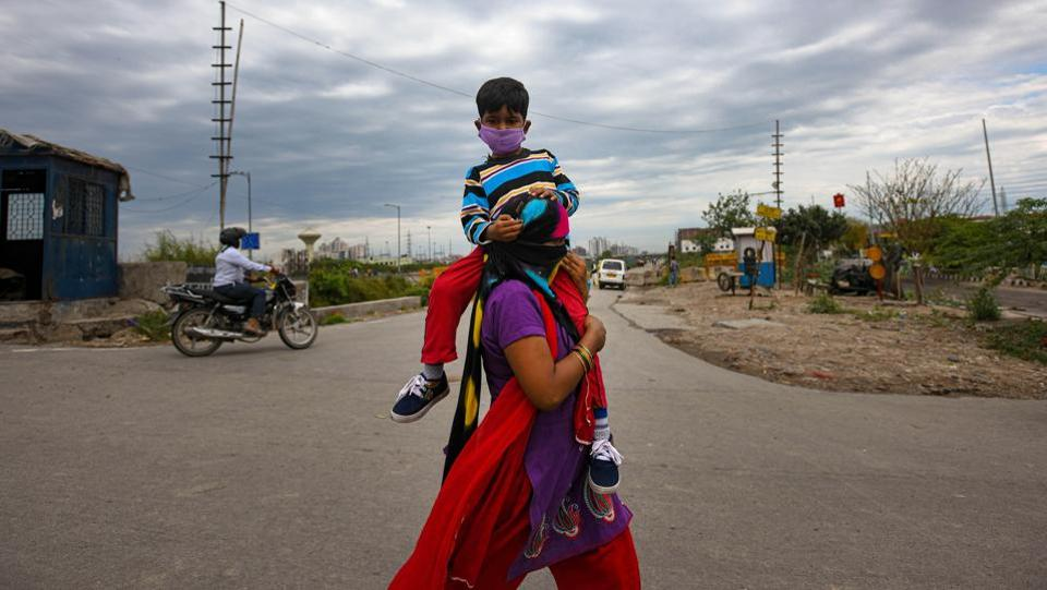 Mamta, 32, carries her 5 year old son Yuvraj as they head toward their home town Aligarh on the third day of the 21-day national lockdown imposed by Prime Minister Narendra Modi to curb the spread of coronavirus, at Ghazipur, in New Delhi. (Amal KS / HT Photo)