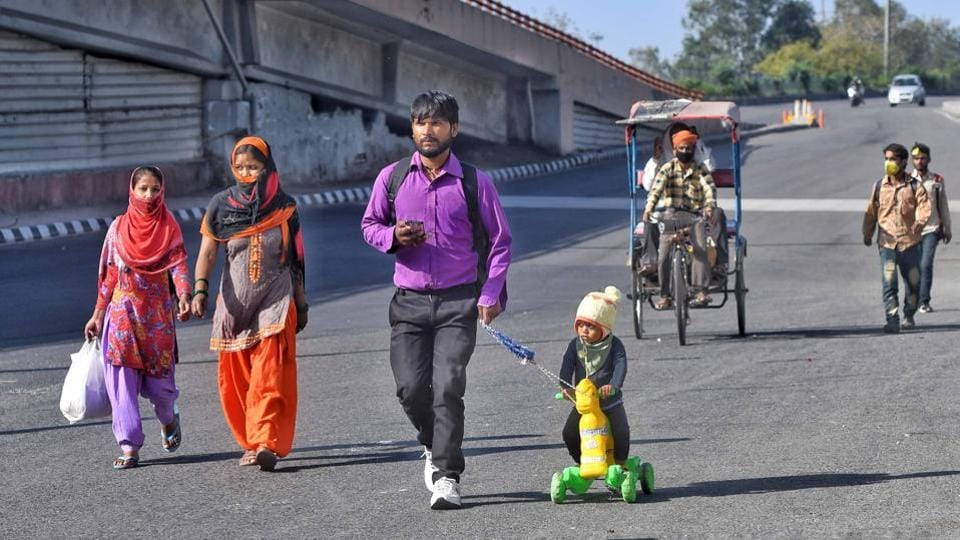 Ranjit Rajput, 28, a migrant worker from Bareilly walks back to his hometown with his son Prince, 4, on Saturday, March 28. (Biplov Bhuyan / HT Photo)