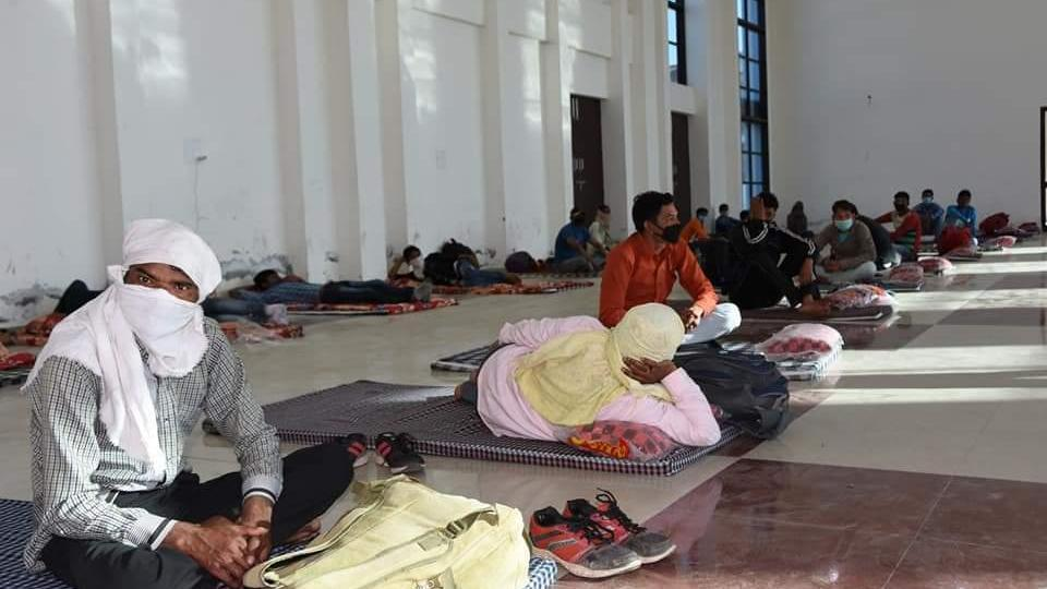 People relax at a temporary shelter home in Karnal on Sunday.