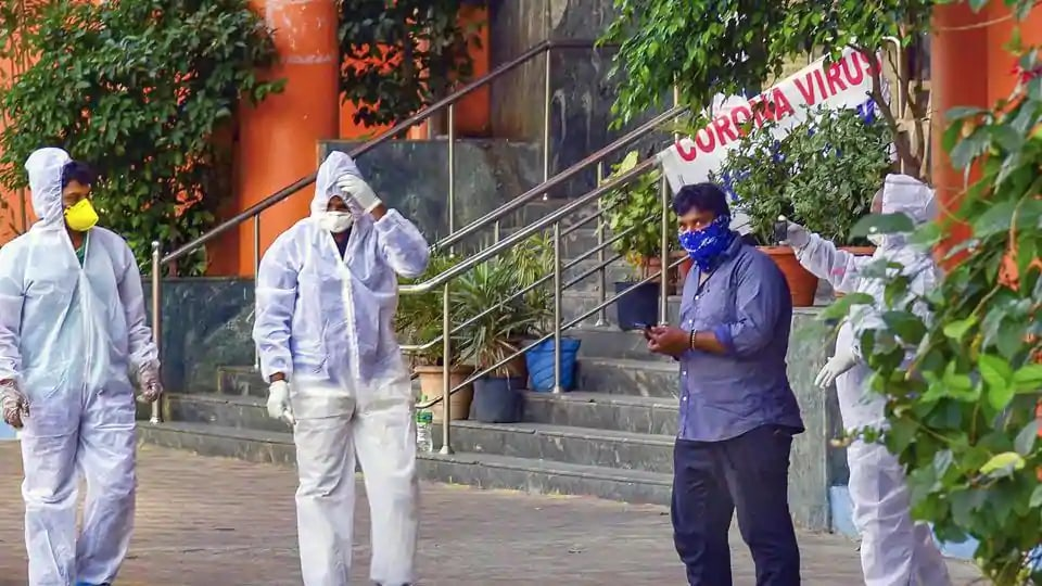 Medical staff members wear masks and protective suits to mitigate the spread of coronavirus.