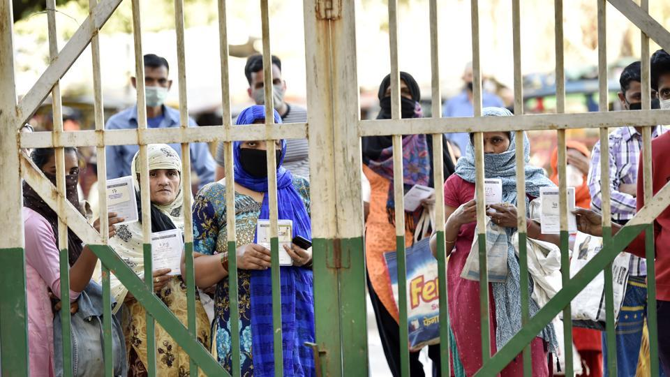 People queue outside a Public Distribution Shop (PDS) shop in New Delhi to collect their ration under the public distribution scheme by Delhi Government, on day 5 of the 21 day national lockdown imposed by PM Narendra Modi.