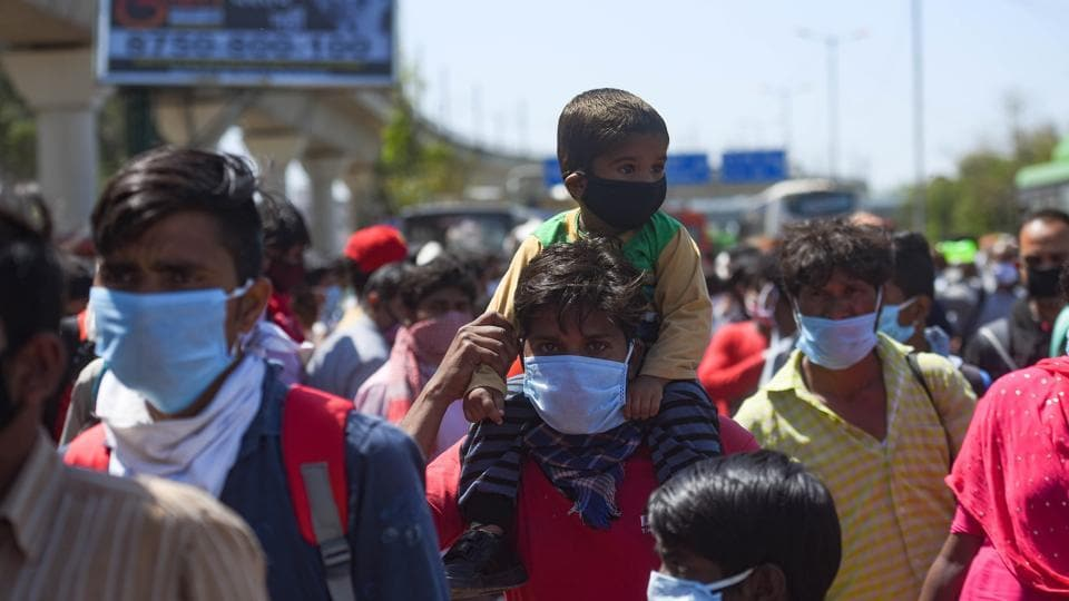 A man seen carrying a child on his shoulder as a large number of migrant workers head home on day 5 of the 21 day nationwide lockdown to curb the spread of coronavirus.
