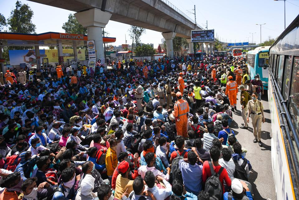 NDRF personnel offers hand sanitizer to migrant workers assembled outside Anand Vihar Bus Terminus on Day 5 of the 21-day nationwide lockdown imposed by PM Narendra Modi to curb the spread of coronavirus, in New Delhi, India, on Sunday, March 29, 2020.