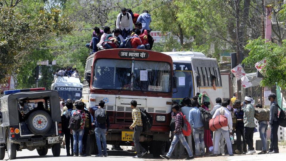 Migrant workers try to board an overcrowded bus to return to their home on day 5 of the 21-day nationwide lockdown to curb the spread of coronavirus.