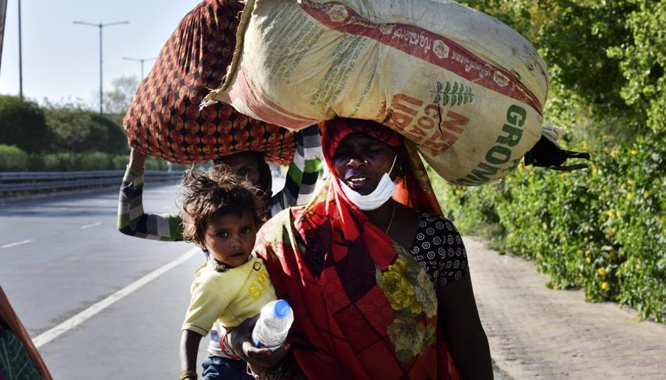 Migrant workers head home on Day 5 of the 21-day nationwide lockdown imposed by PM Narendra Modi to curb the spread of coronavirus, at Greater Noida Expressway, in Noida, India, on Sunday, March 29, 2020.