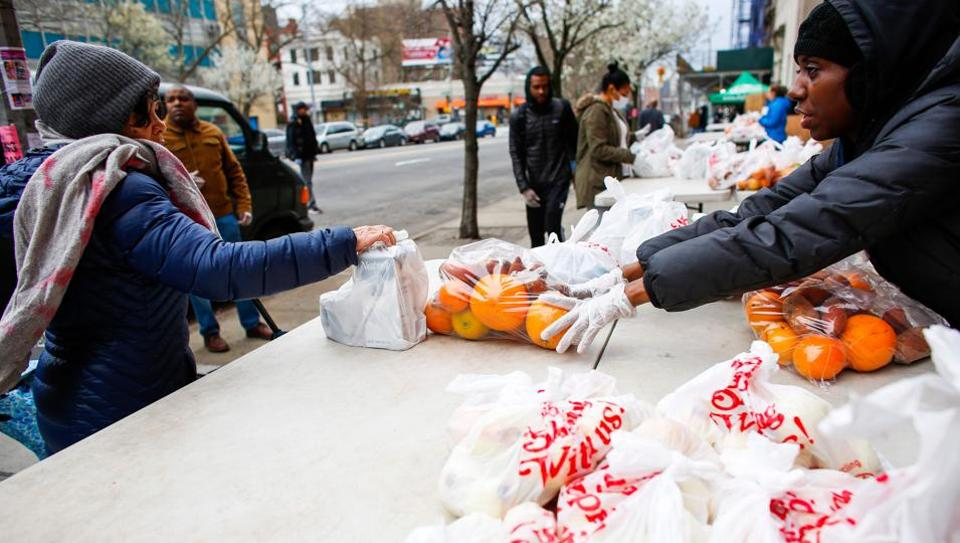 Volunteers from City harvest distribute food in Harlem on March 28, 2020 in New York City.   With tens of thousands of New Yorkers out of work due to the epidemic, New York food banks are facing an influx of newcomers who never before would have needed them.