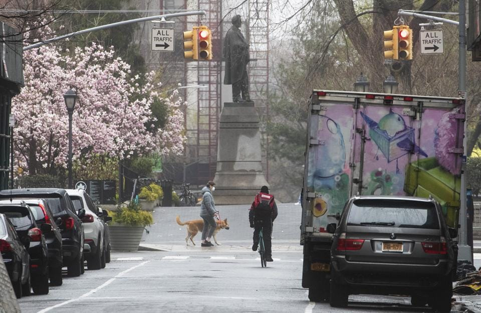 A cyclist and a dog walker are seen along West 16th Street near Union Square, Sunday, March 29, 2020, in New York.