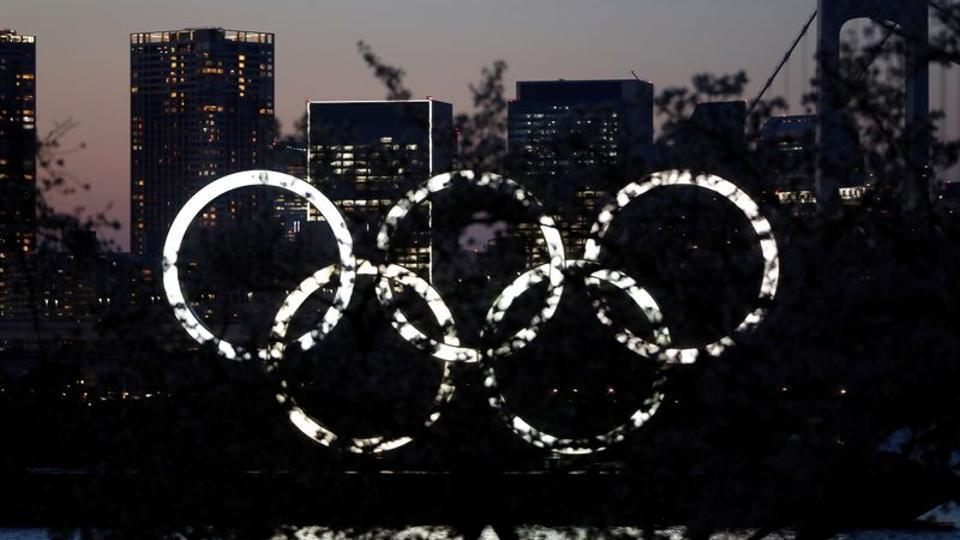 The giant Olympic rings are seen in the dusk through a tree at the waterfront area at Odaiba Marine Park after postponing Games due to the outbreak of coronavirus disease (COVID 19), in Tokyo, Japan March 25, 2020.