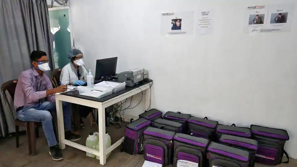 Laboratory technicians sit next to boxes containing coronavirus disease (COVID-19) testing kits at a sample collection centre in Ahmedabad.
