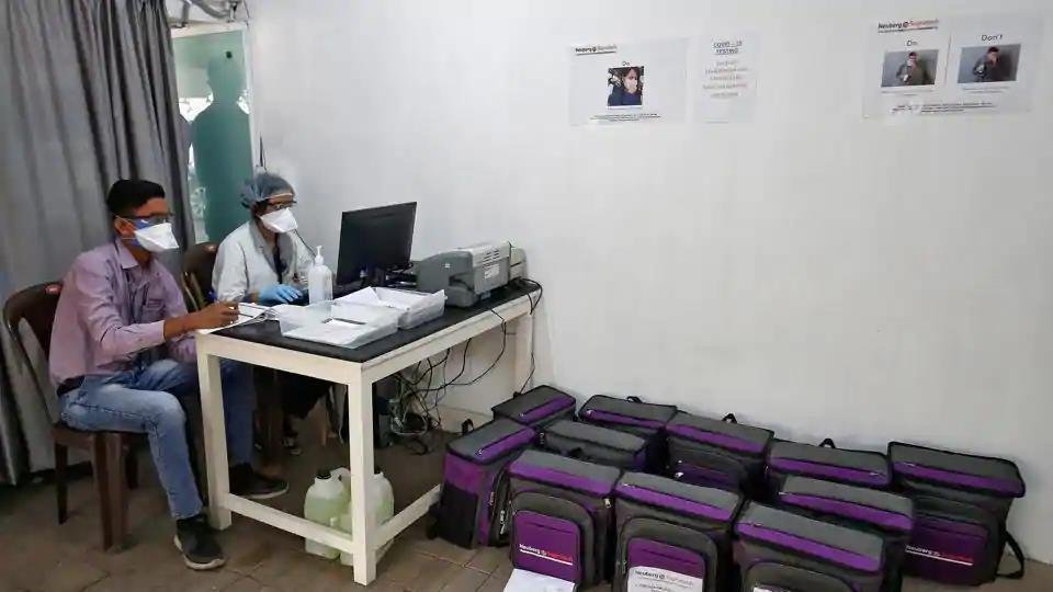 Laboratory technicians sit next to boxes containing coronavirus disease (COVID-19) testing kits at a sample collection centre in Ahmedabad