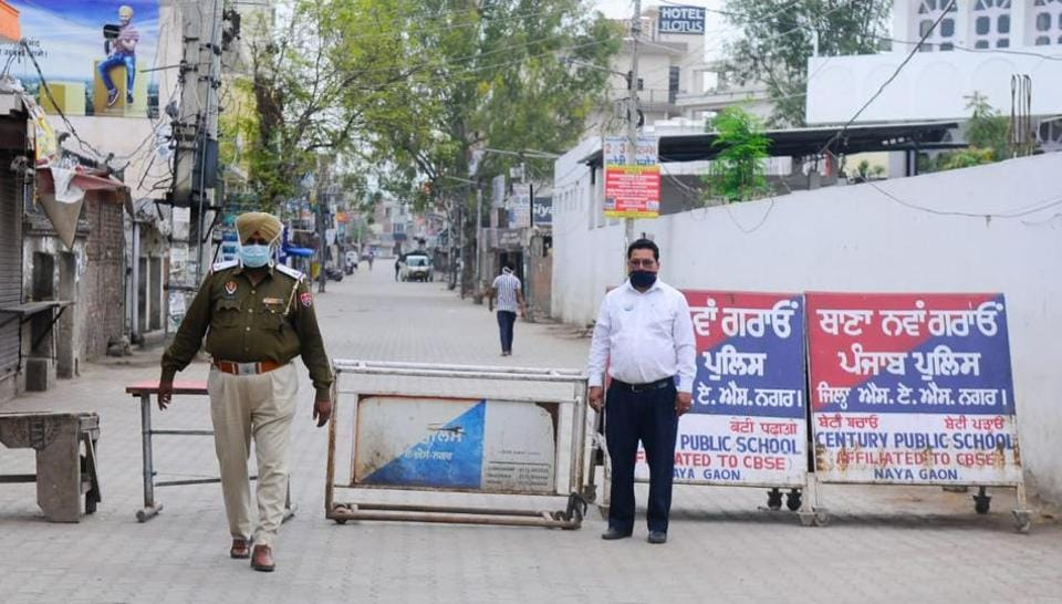 Punjab Police personnel after sealing a road leading to Dasmesh Nagar in Nayagaon town of Mohali district after the death of a 65-year-old coronavirus patient from the area at Post Graduate Institute of Medical Education and Research, Chandigarh, on Tuesday.