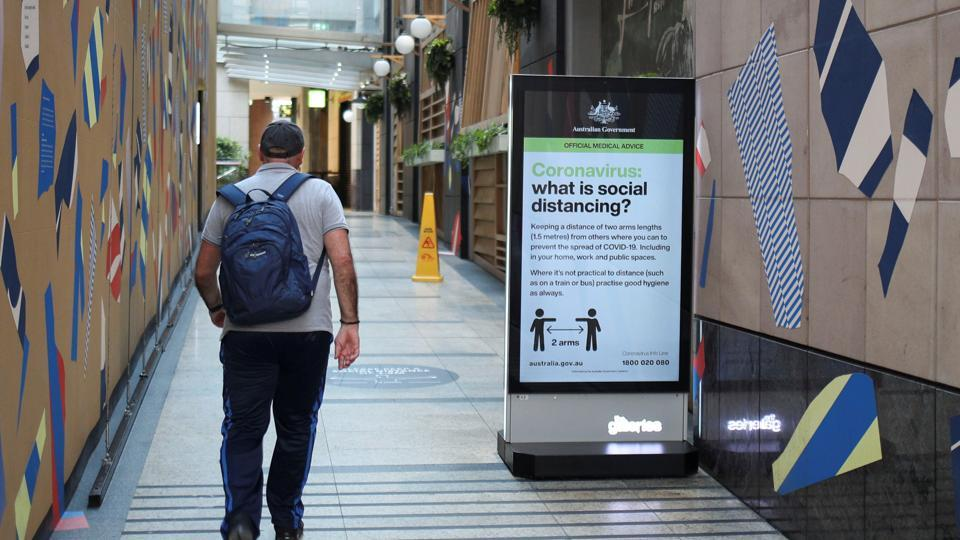 A man walks in a corridor near a sign with instructions about the coronavirus and social distancing in Sydney, on March 31.