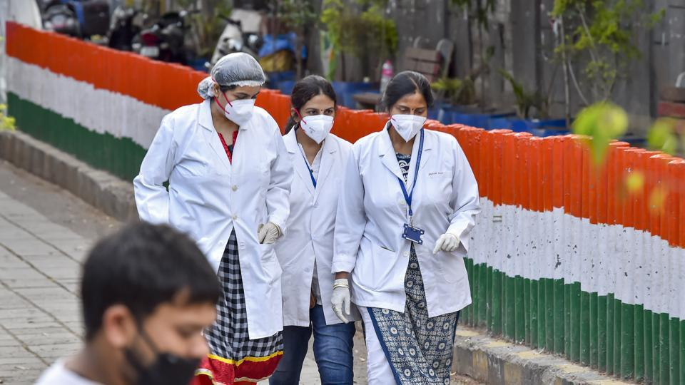 Medics, wearing masks, walk as the police cordoned off an area in Nizamuddin after some people showed coronavirus symptoms, in New Delhi.